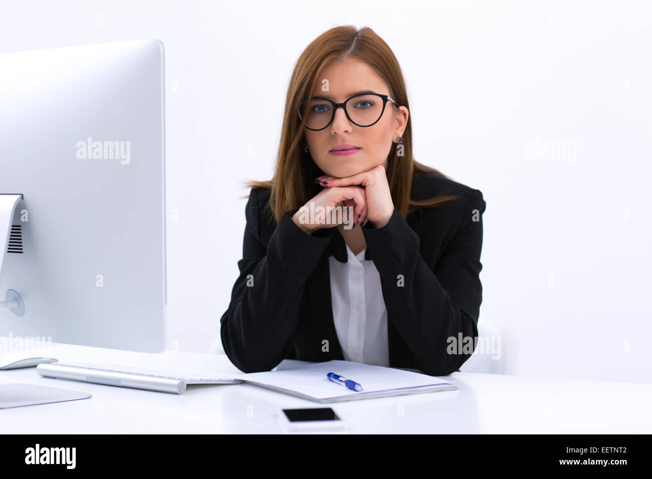 Portrait of a beautiful young businesswoman sitting at her workplace in office - Stock Image