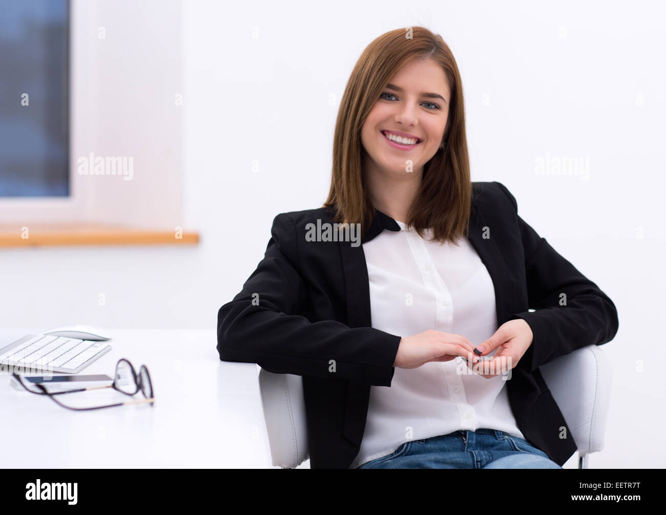 Portrait of a beautiful smiling woman sitting in the office - Stock Image
