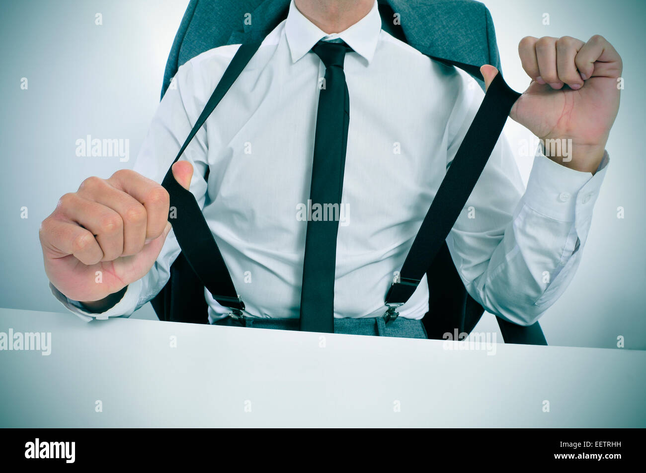 a young businessman in suspenders sitting at his office desk - Stock Image