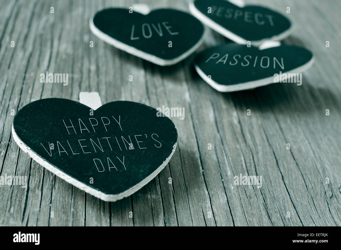 words love, respect and passion, and the sentence happy valentines day written in some heart-shaped chalkboards, - Stock Image
