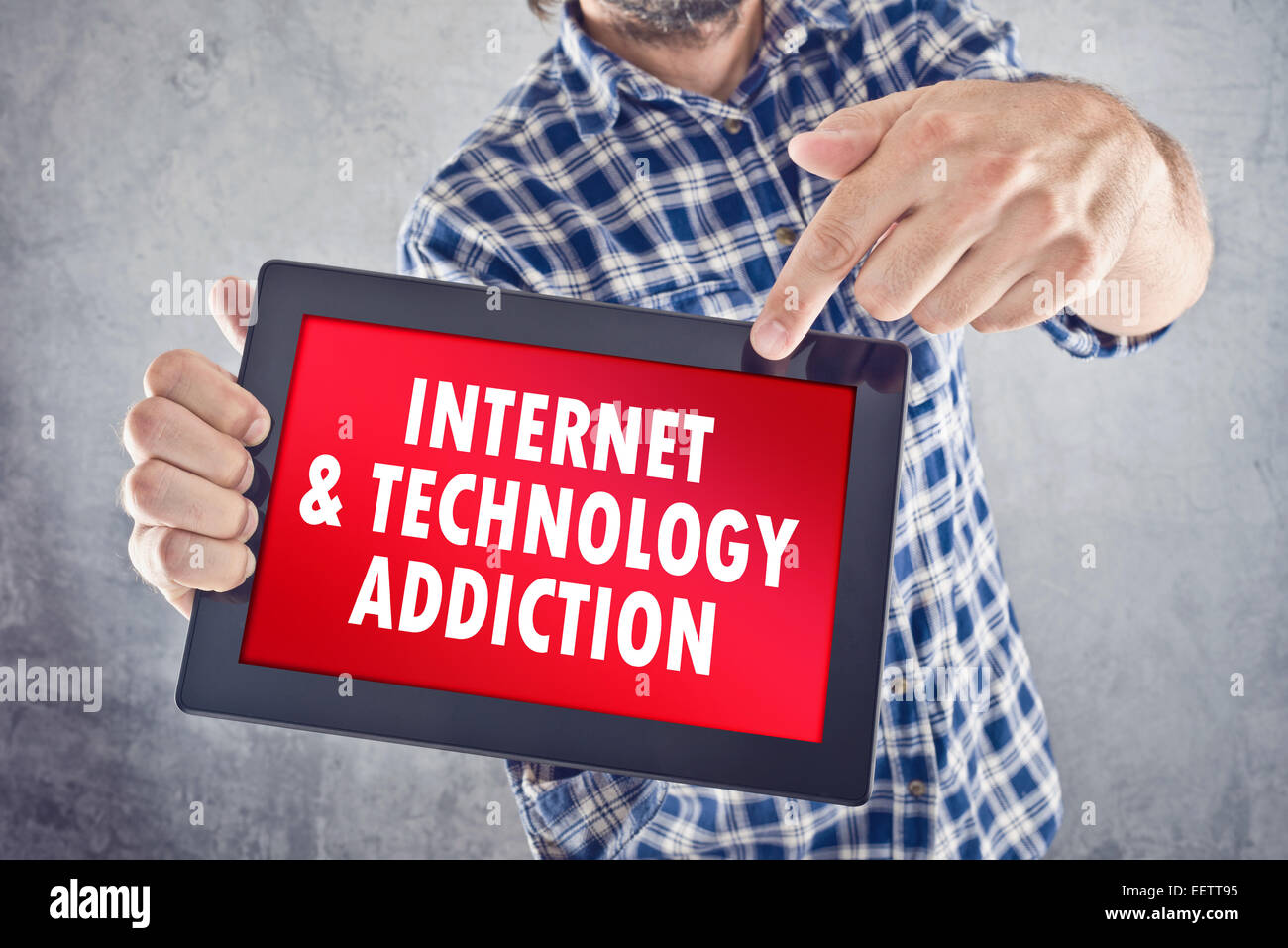 Casual man pointing to 10 inch display of digital tablet with Internet and Technology Addiction displayed on the - Stock Image
