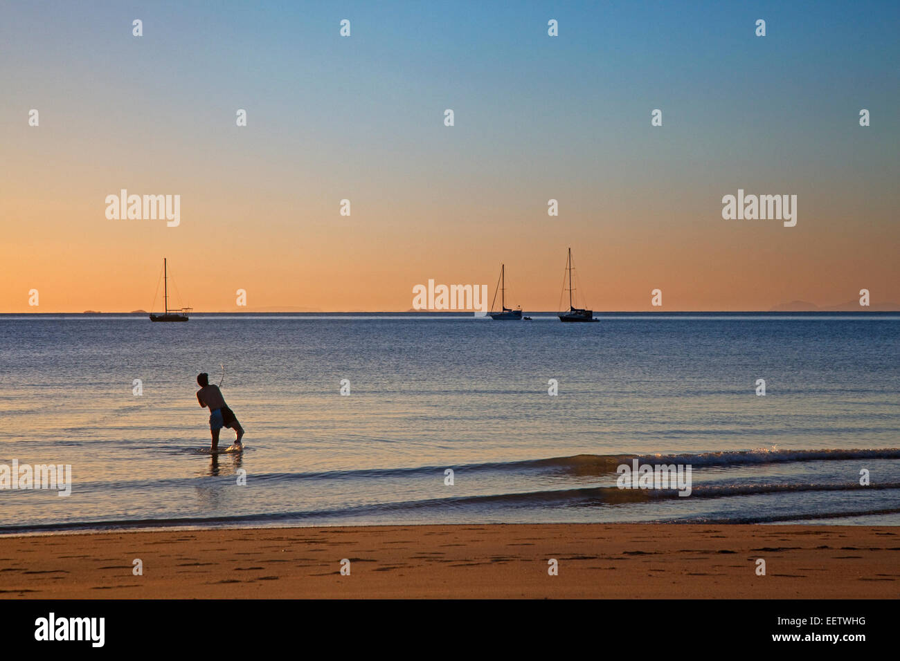 Sailing boats at sunset and sea angler fishing from the beach at Horseshoe Bay on Magnetic Island along the Coral - Stock Image