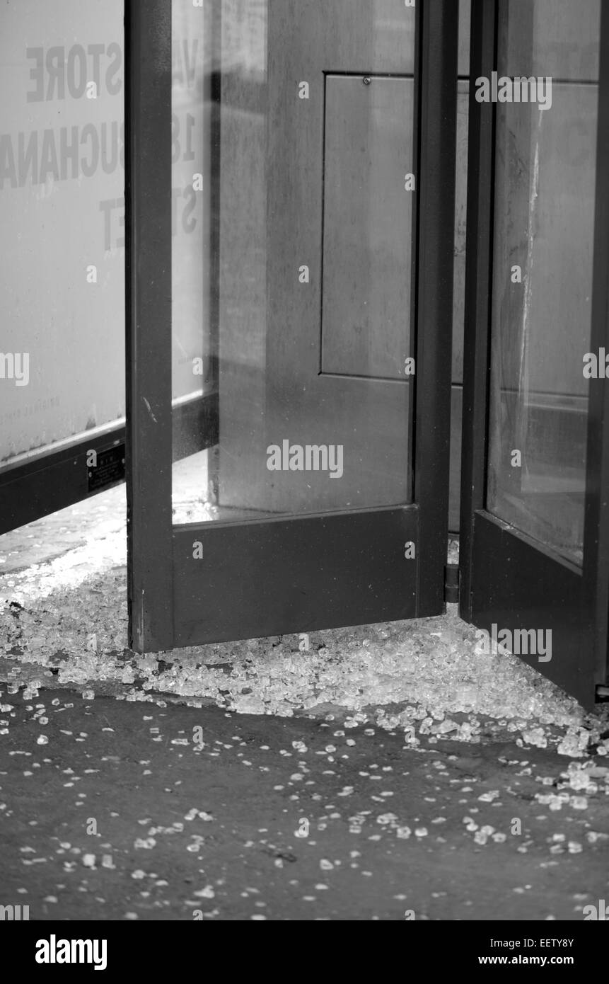 Broken glass in a telephone boc in Glasgow city centre - Stock Image