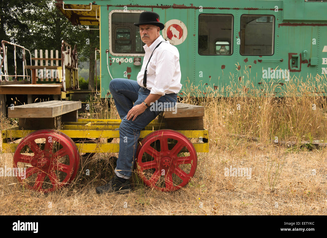 Mature male in bowler hat sitting on a railway car - Stock Image