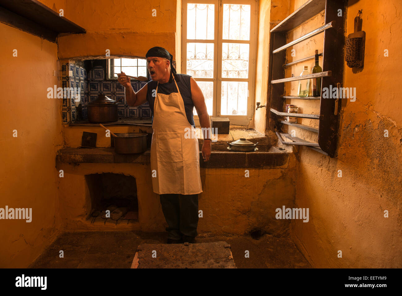 Male cook tasting soup in an old-fashioned kitchen Stock Photo