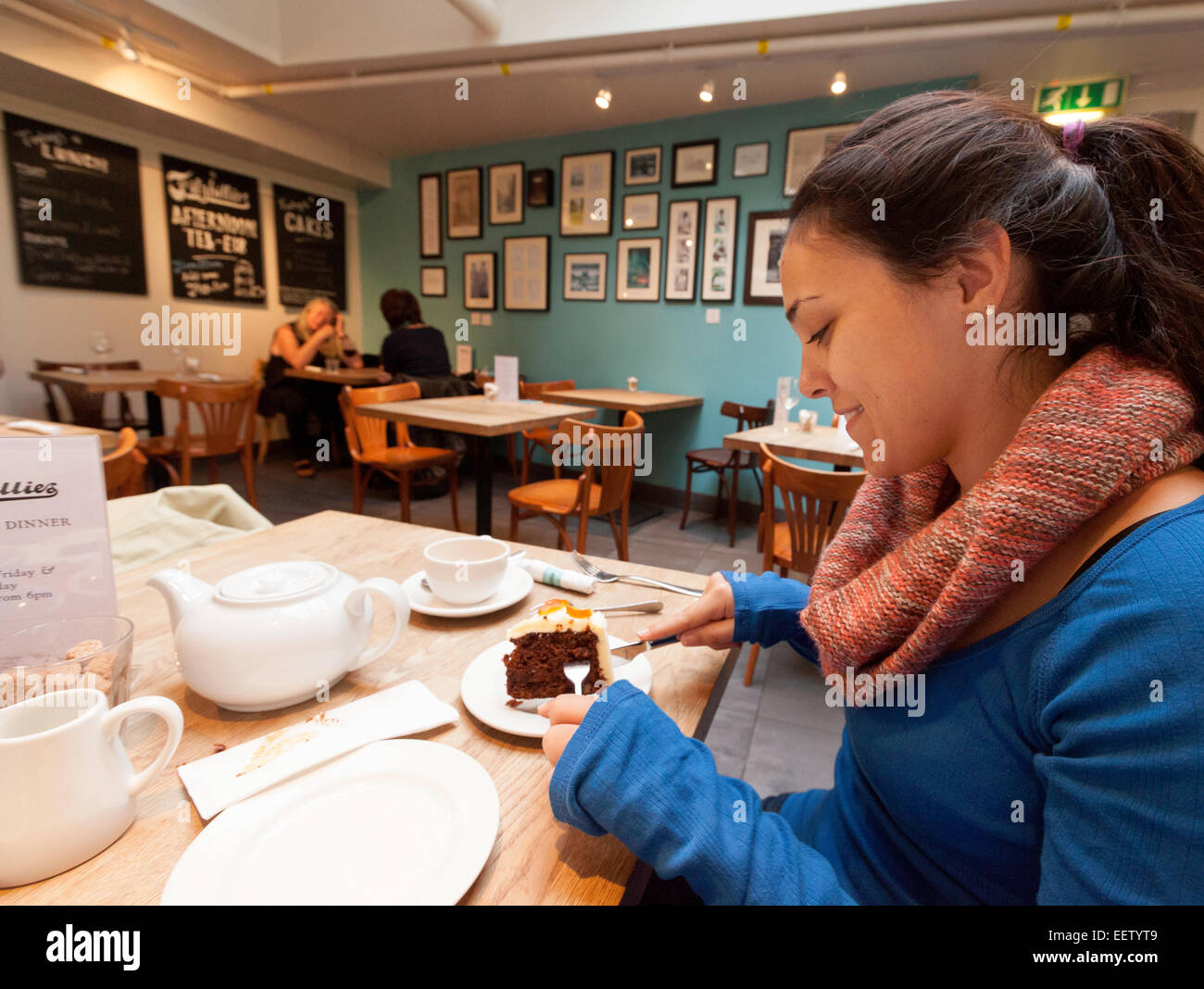 A young woman eating a cake, the interior, Fitzbillies cake shop, Cambridge England UK Stock Photo