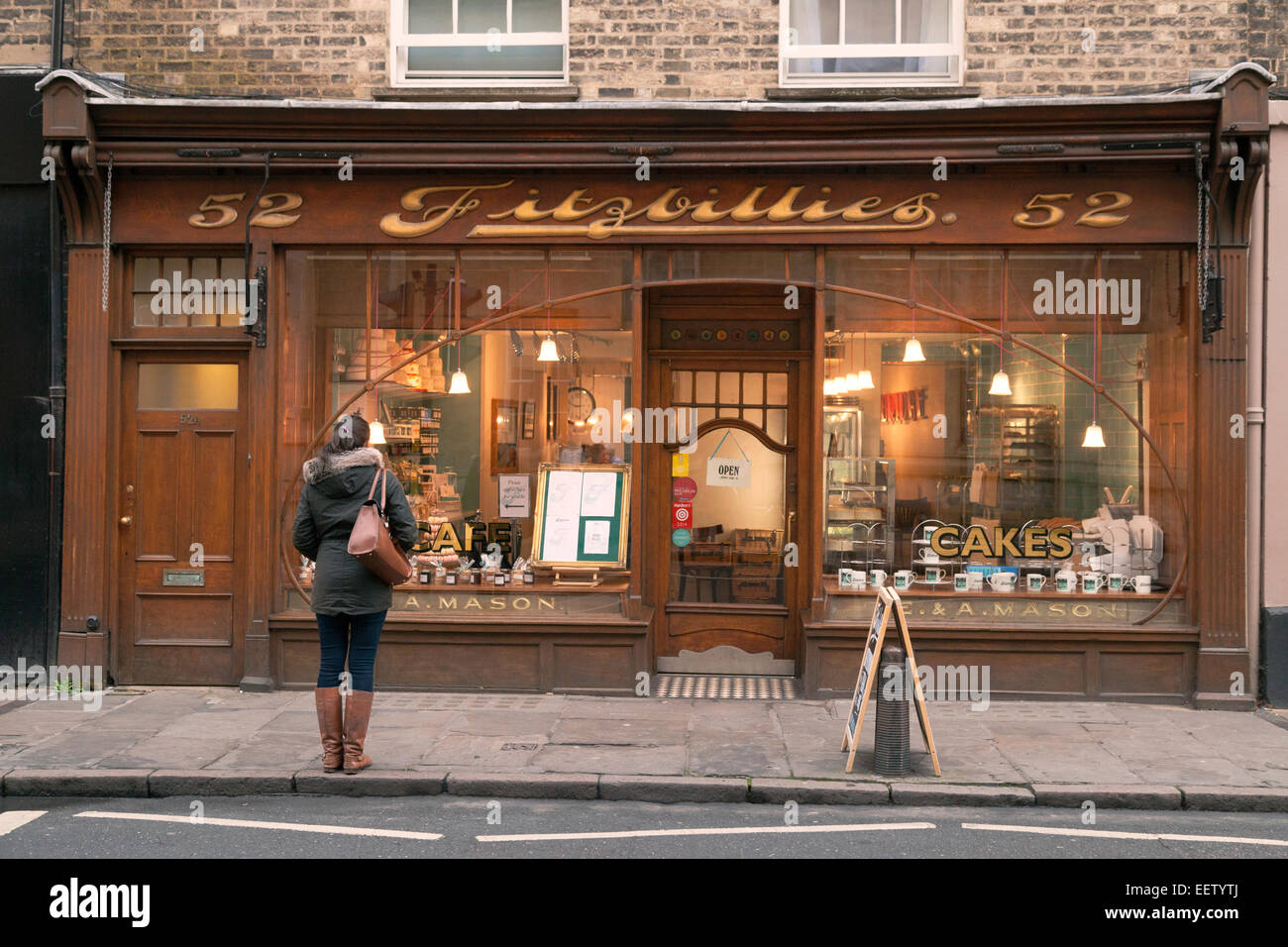 A young woman outside Fitzbillies cake shop or cafe, Cambridge England UK Stock Photo