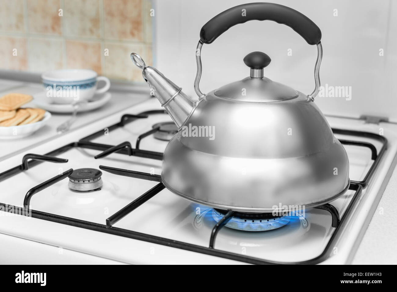 kettle on a gas stove flame burn not boiling - Stock Image