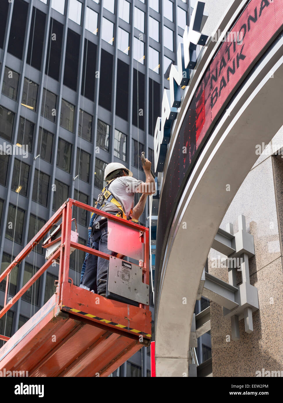 Bank Repair . A worker wields a hammer as he works on the repair or installation of a sign in front of a bank. Downtown, - Stock Image