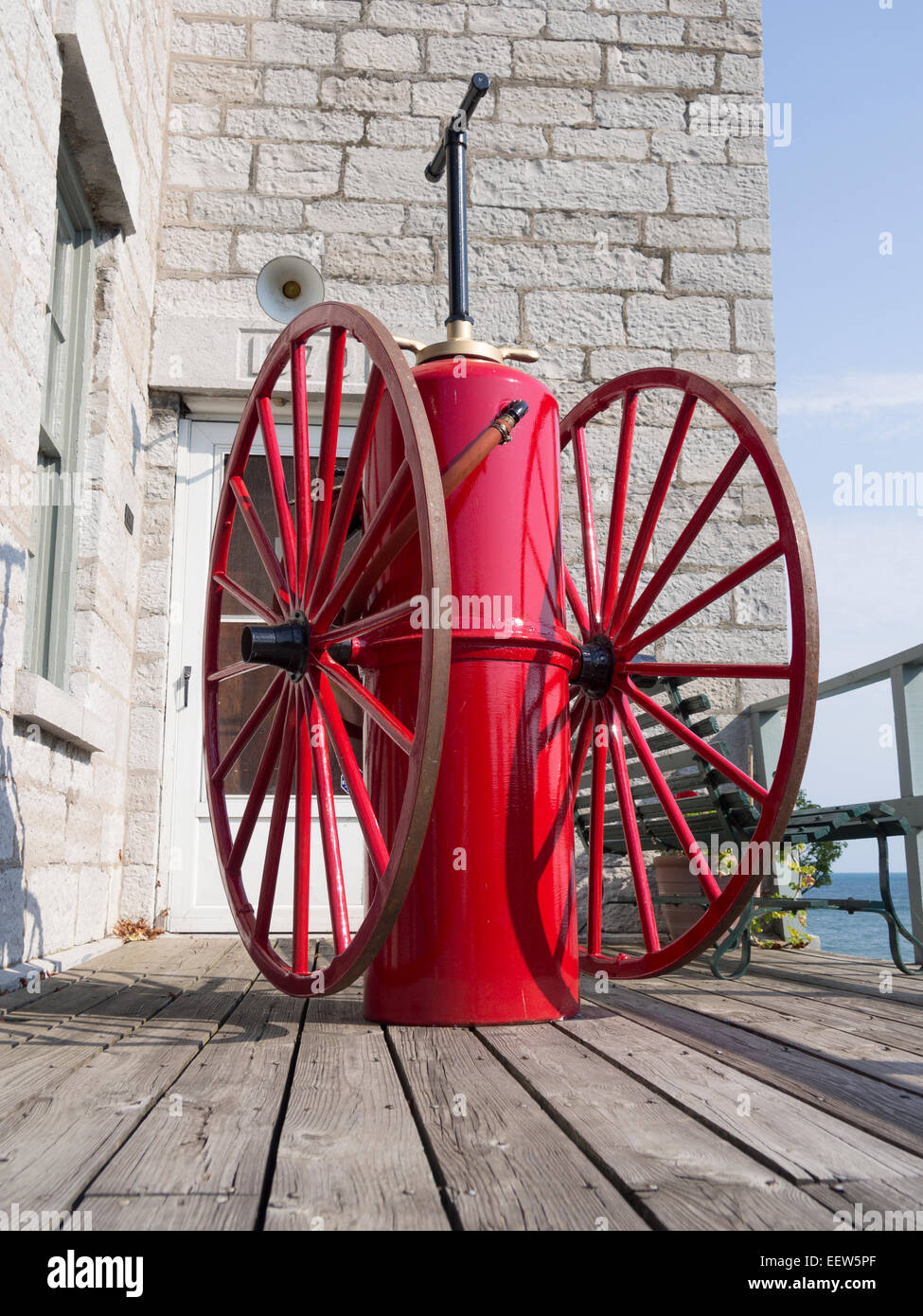 Antique fire fighting equipment in red. Antique hand pumped pressure tank on wheels for fire fighting on the porch - Stock Image