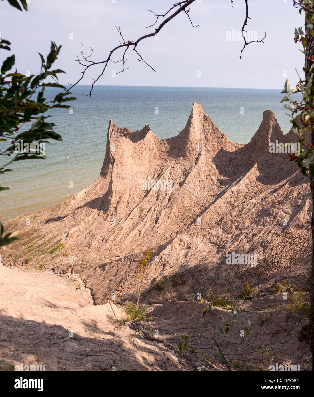 Clay Bluffs eroding along the shore of Lake Ontario. Pink chimneys of peaked clay formed as a result of erosion - Stock Image