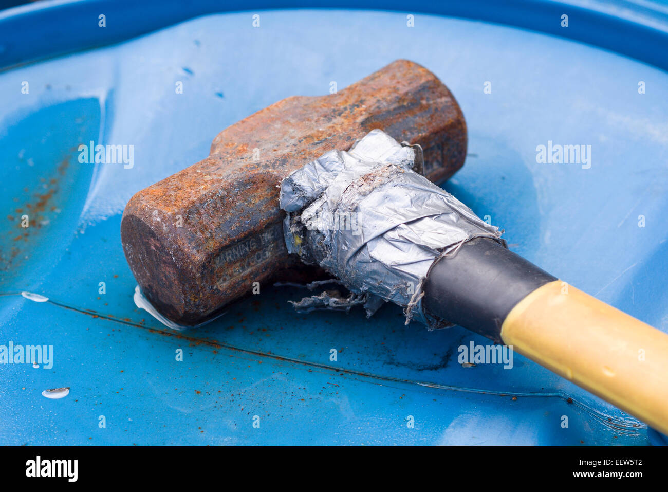 Rusty Sledge Hammer fixed with duct tape. A rusted sledge rests on a blue plastic barrel. Its handle repaired w - Stock Image
