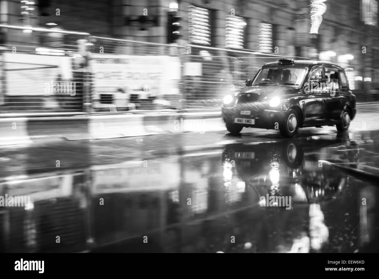 An English taxi makes it's way through the rain. - Stock Image