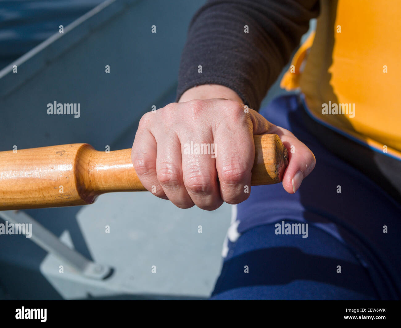 Hand holding an Oar and Rowing. A woman's hand on an boat's oar, rowing the boat. - Stock Image
