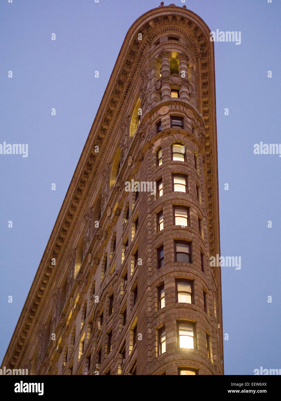 The sharp corner of New York's Flatiron Building. An evening shot of this iconic building. Lights glow from - Stock Image