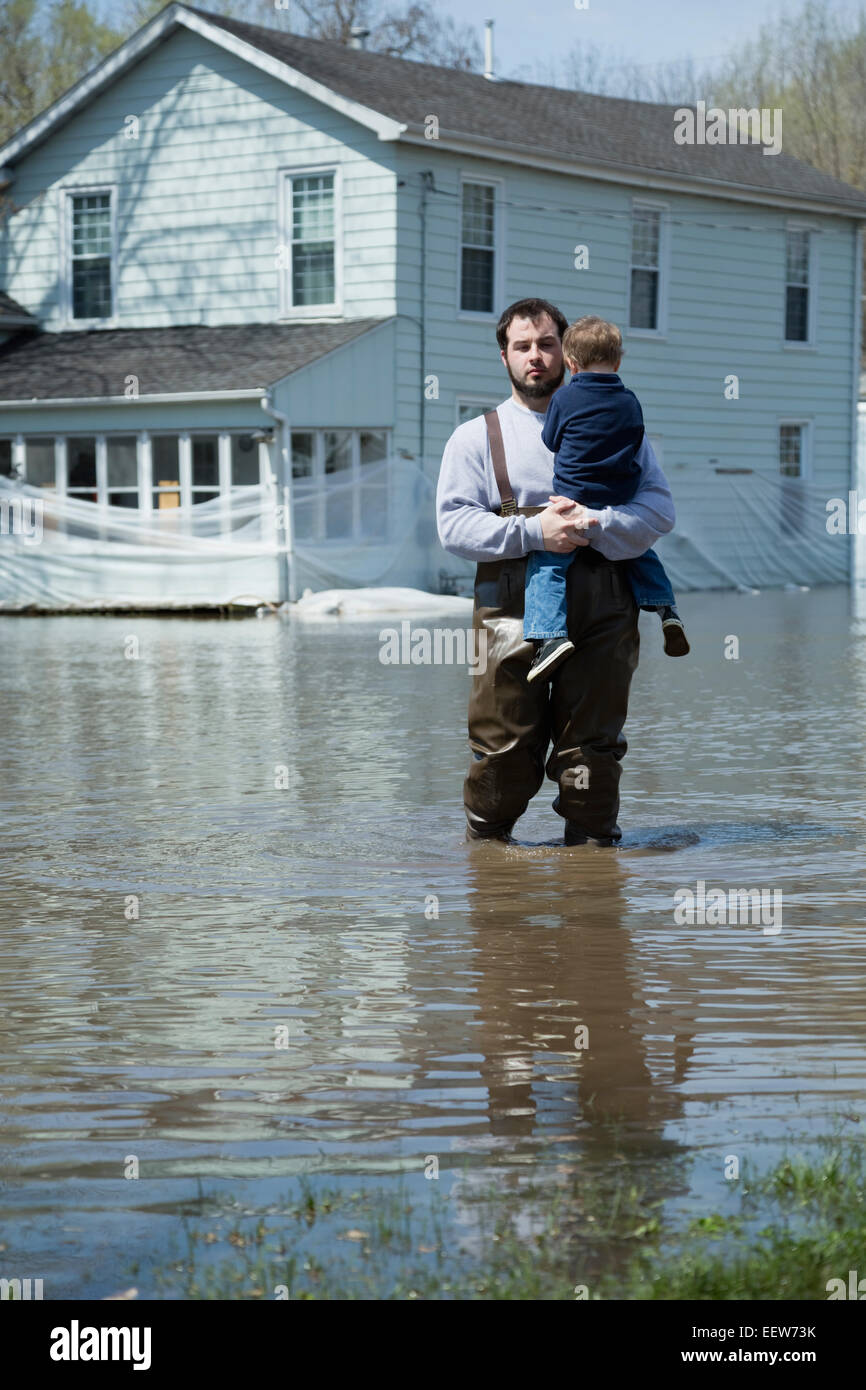 Man with son standing in front of house surrounded by floodwaters Stock Photo