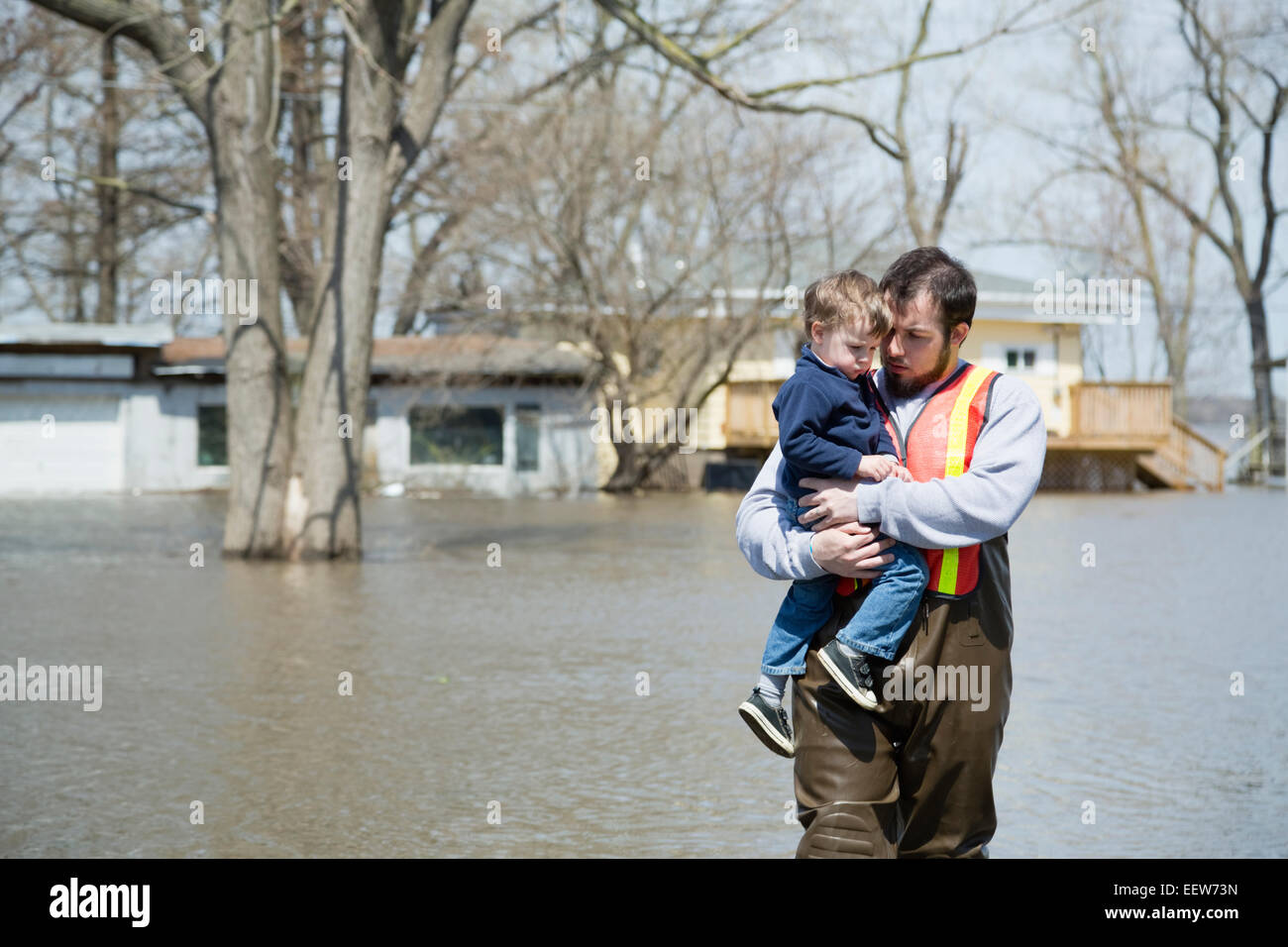Man with son wading in floodwaters Stock Photo