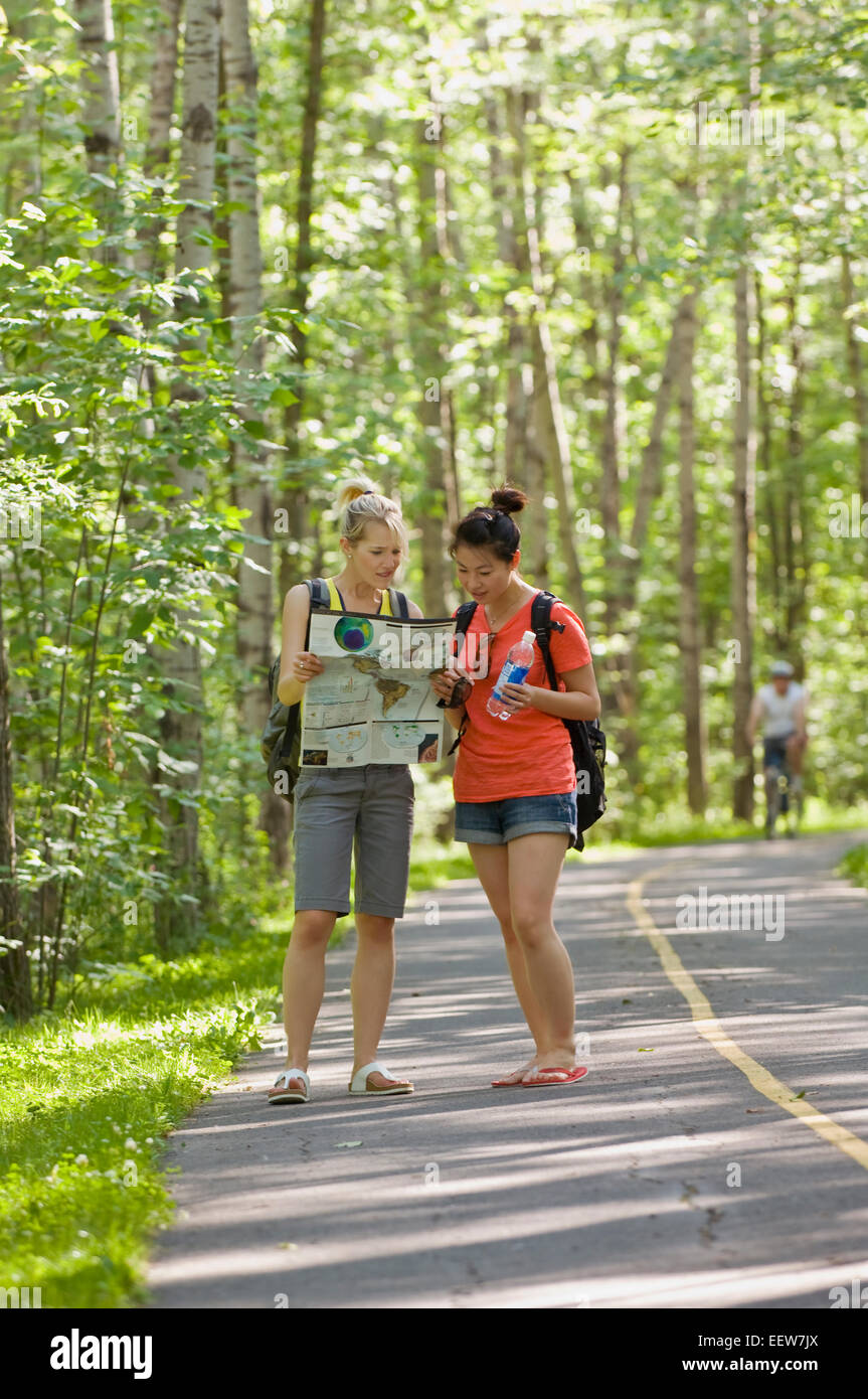 Two girl friends standing on a bike path in the forest and holding a map Stock Photo