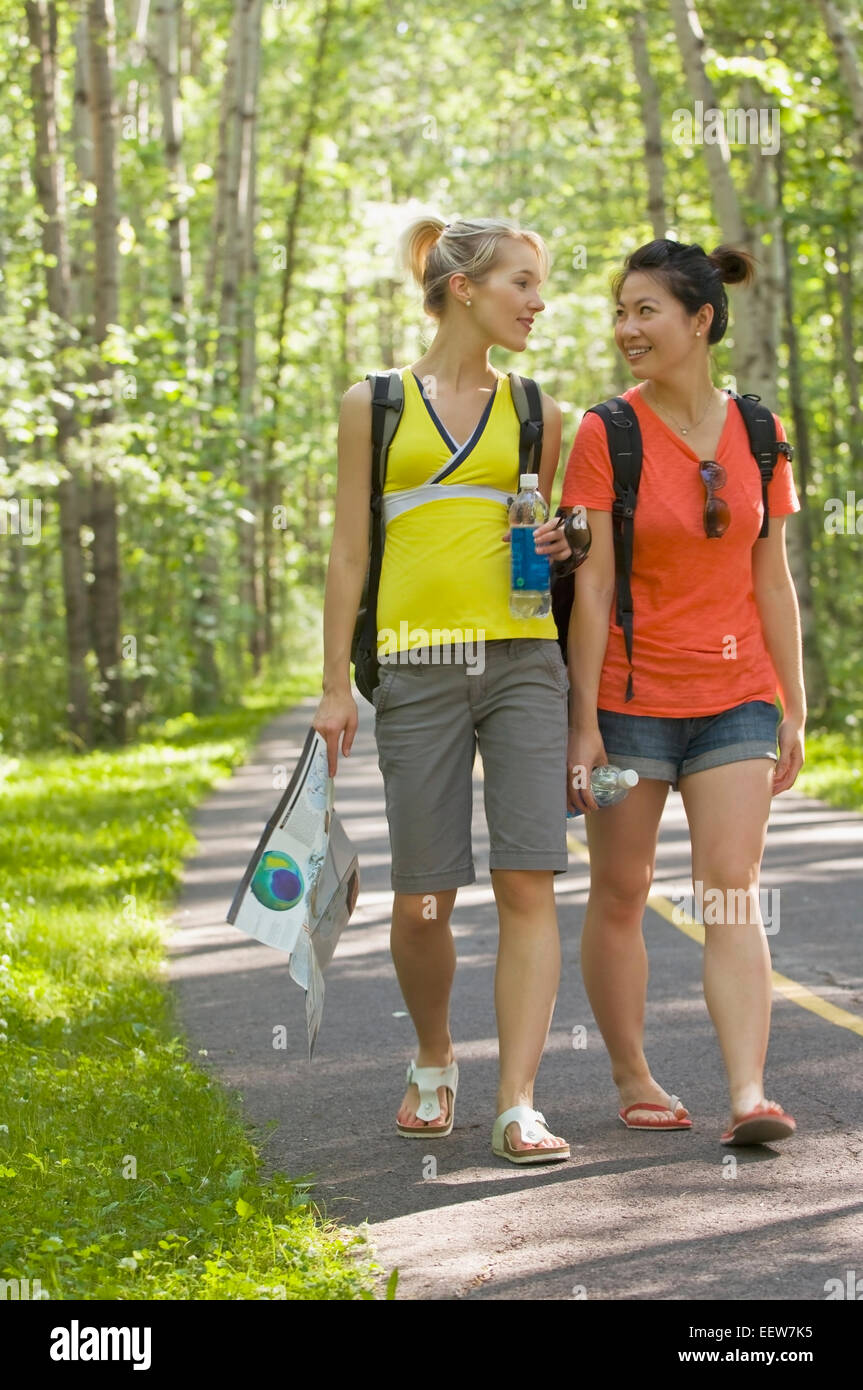 Two girl friends walking on a bike path in the forest with a map Stock Photo