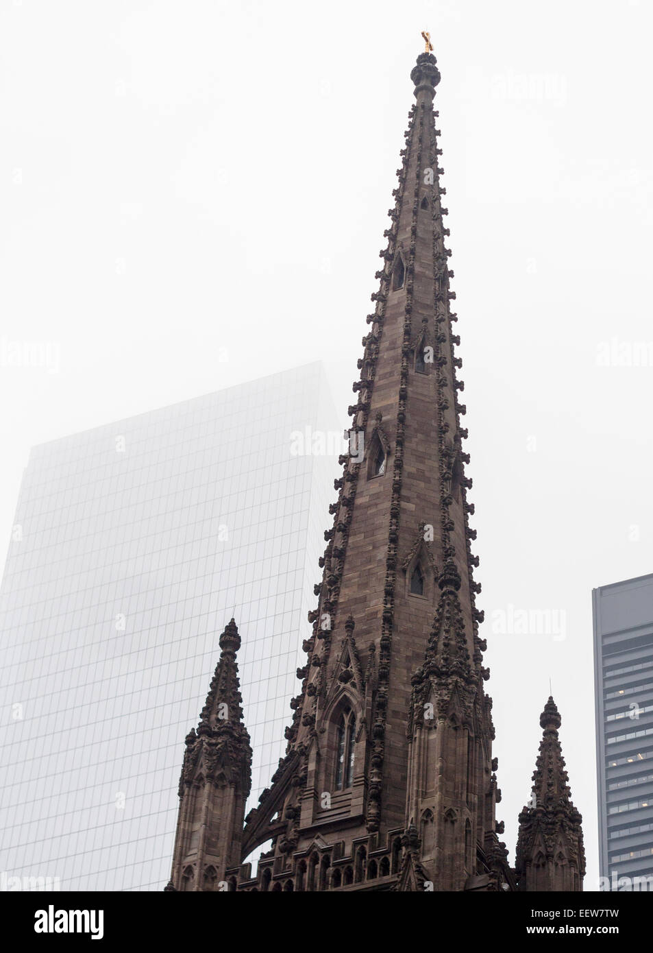 The Spire of Trinity Church in Lower Manhattan: a study in contrasts. The dark stone spire of Trinity topped with - Stock Image