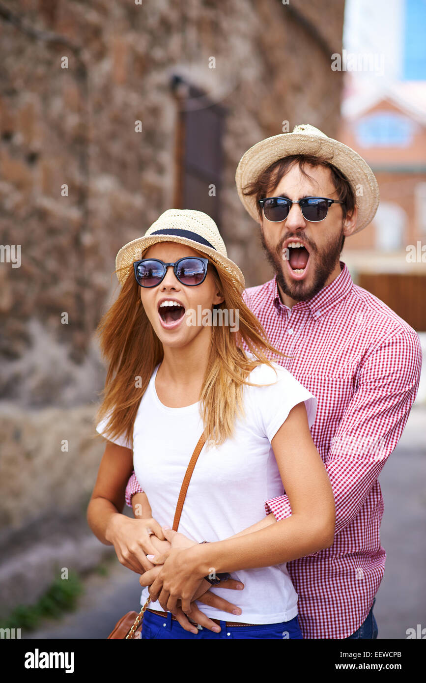 Astonished dates in hats and sunglasses - Stock Image