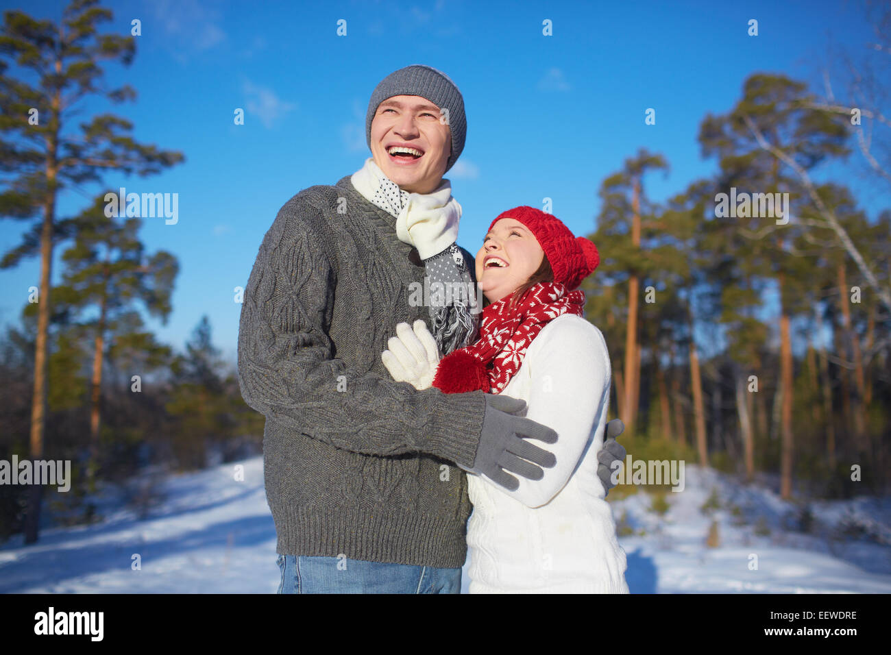 Ecstatic man and woman in knitted winterwear spending leisure in park - Stock Image
