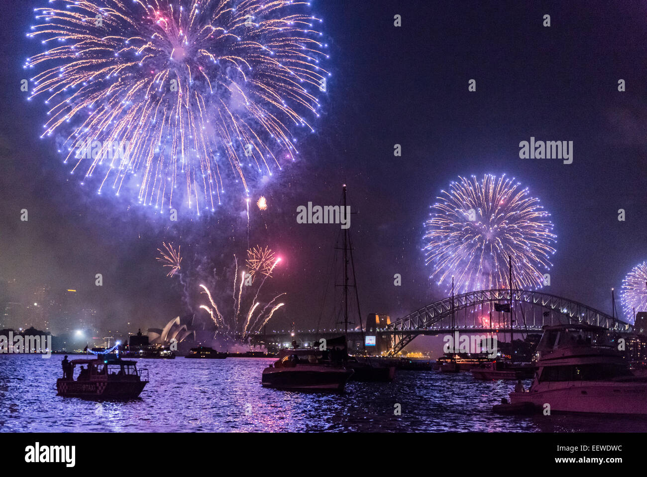 Family Fireworks Display over Sydney Opera House, Harbour Bridge and boats at anchor, New Year's Eve 2014, Sydney - Stock Image