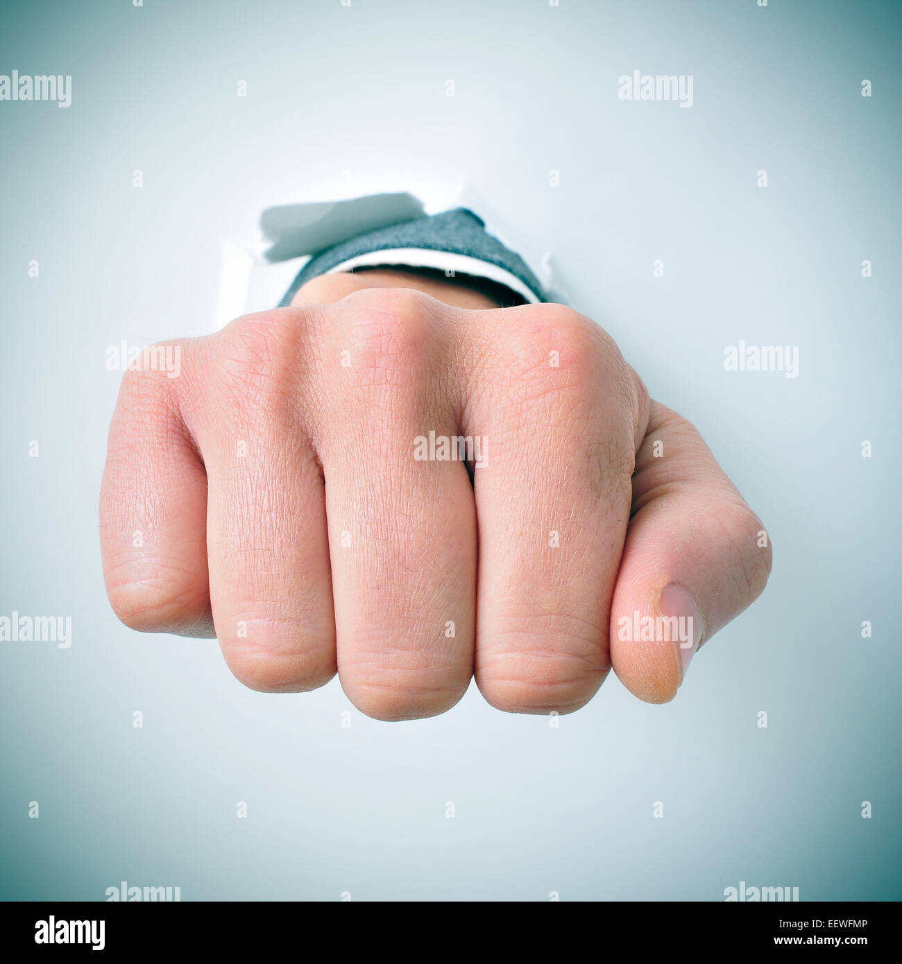 a young businessman breaks through a wall with his fist - Stock Image
