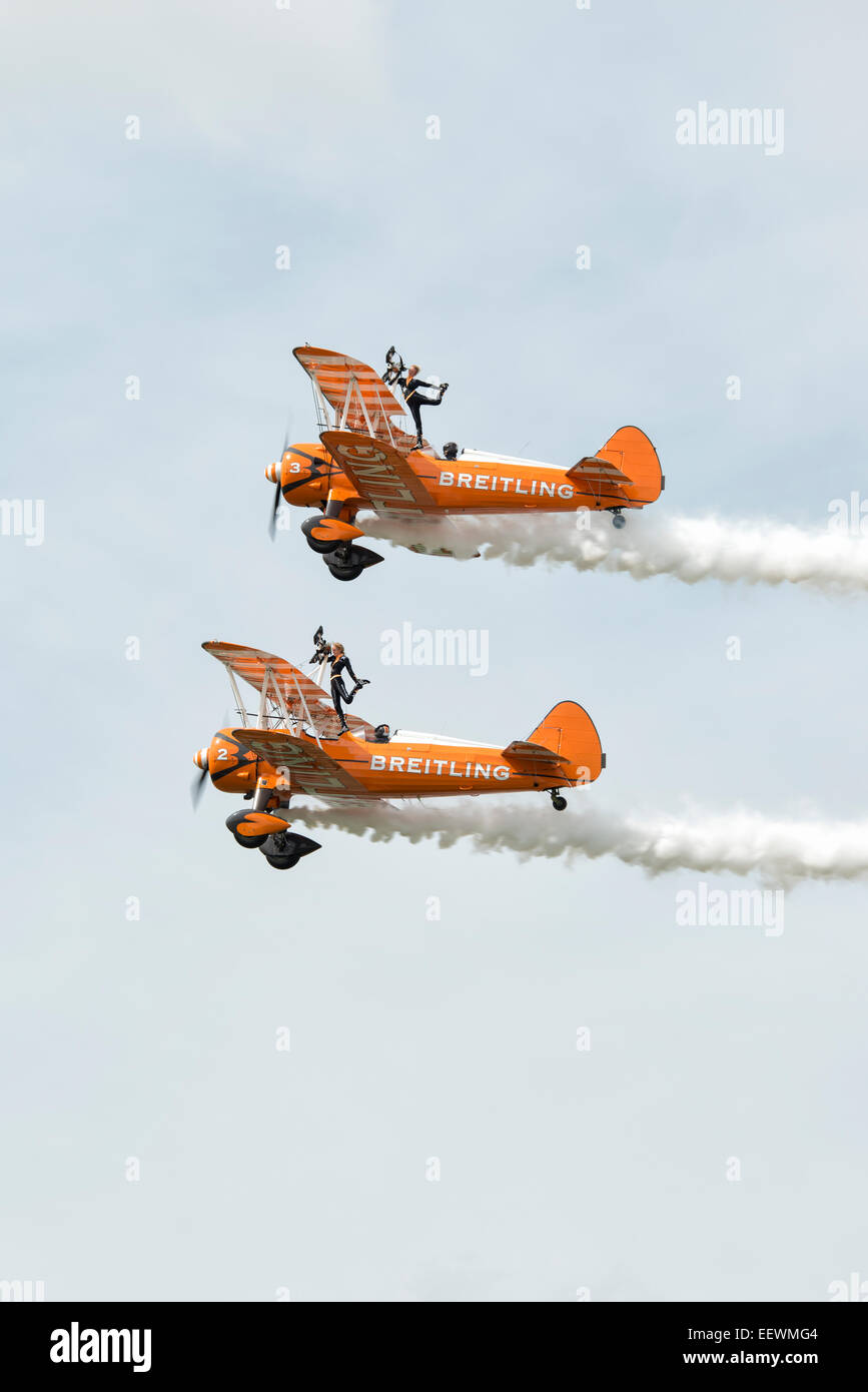 Two Boeing Stearman Biplanes from the AeroSuperBatics Breitling Wingwalking Team make a pass at the RAF Fairford - Stock Image