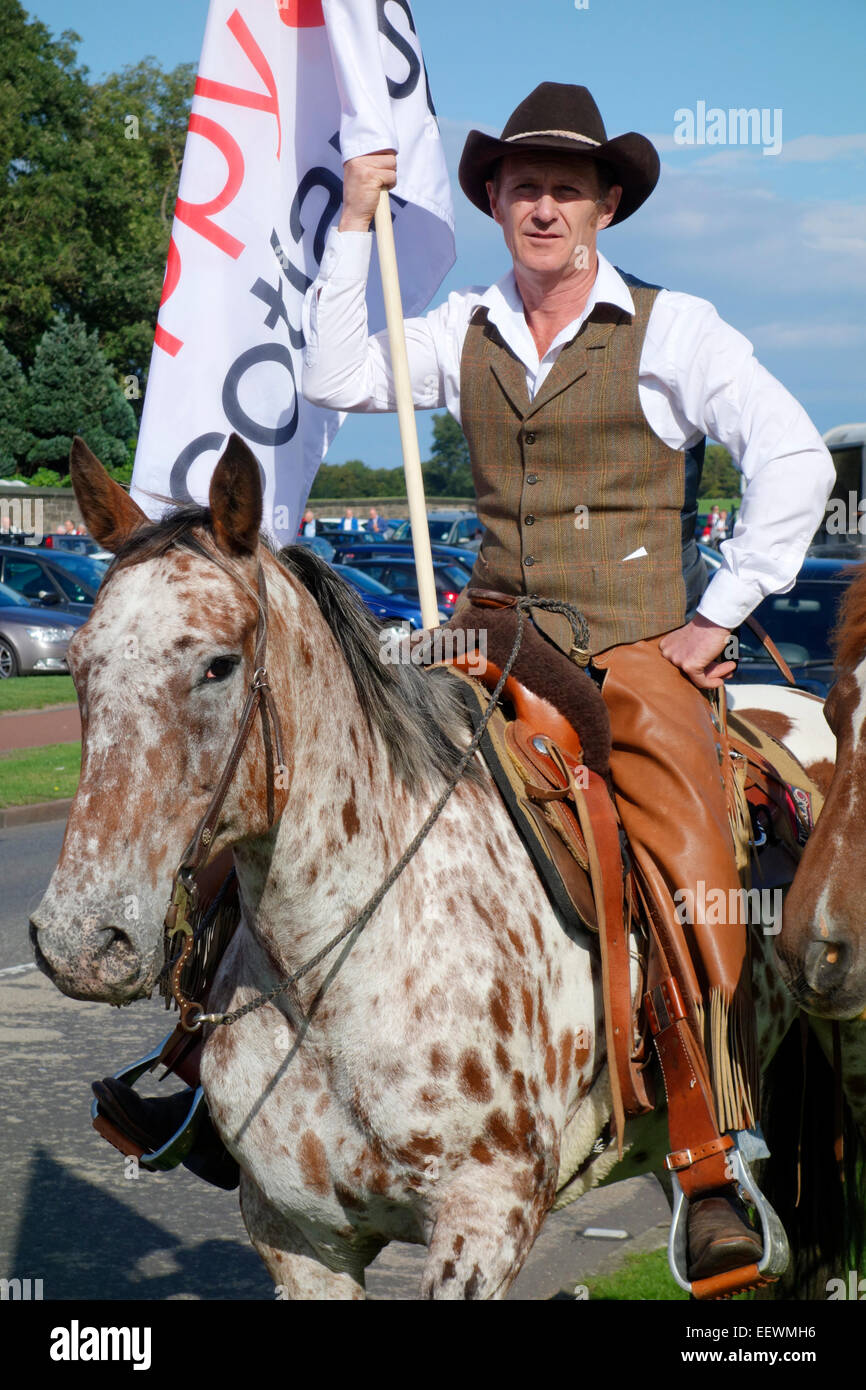 Western rider carrying the Poppyscotland flag during the 2014 Riding of the Marches - Stock Image