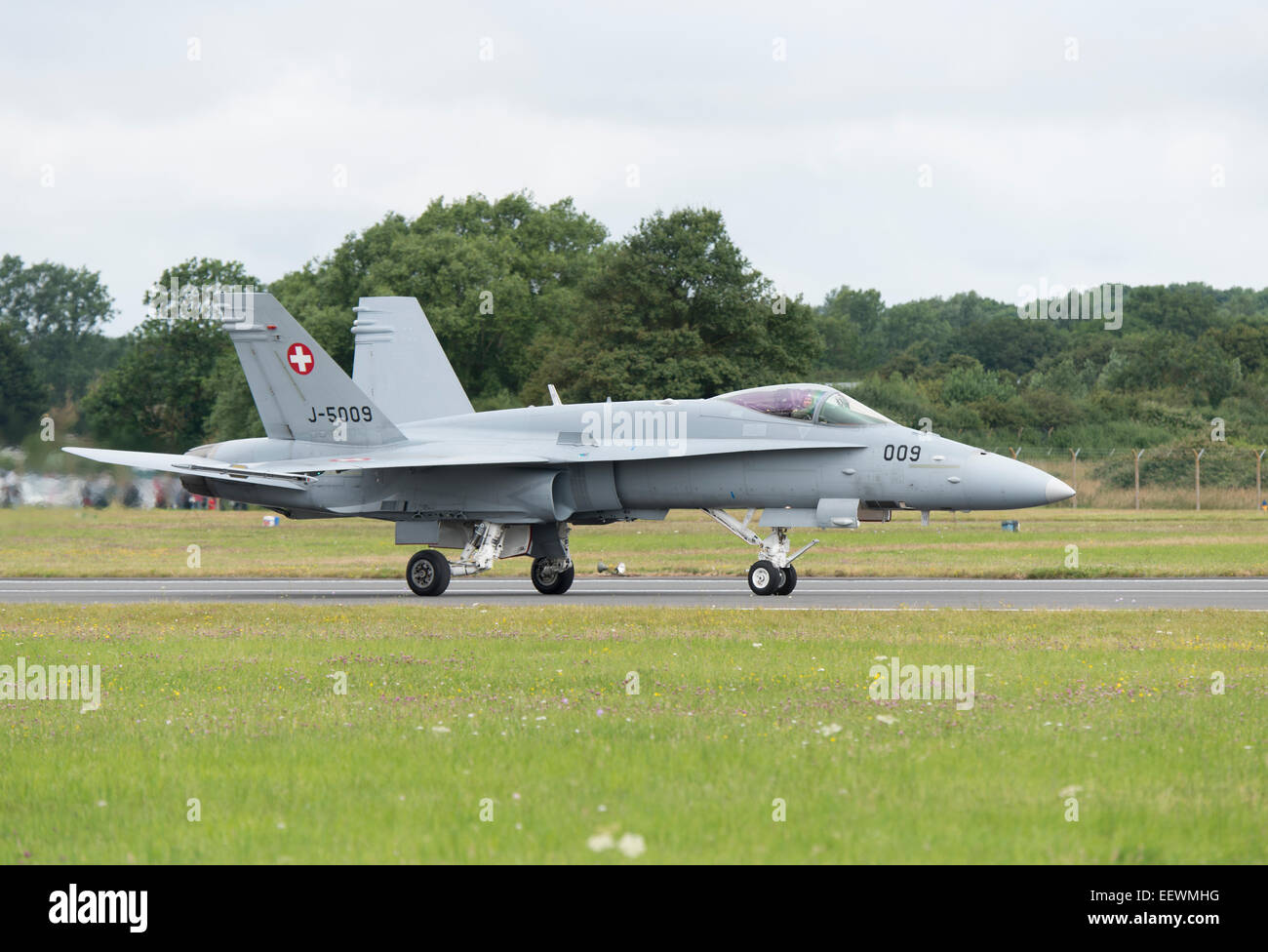 The pilot of the Swiss Air Force F/A-18C Hornet Military Jet Fighter waves to the crowd after completing his display - Stock Image