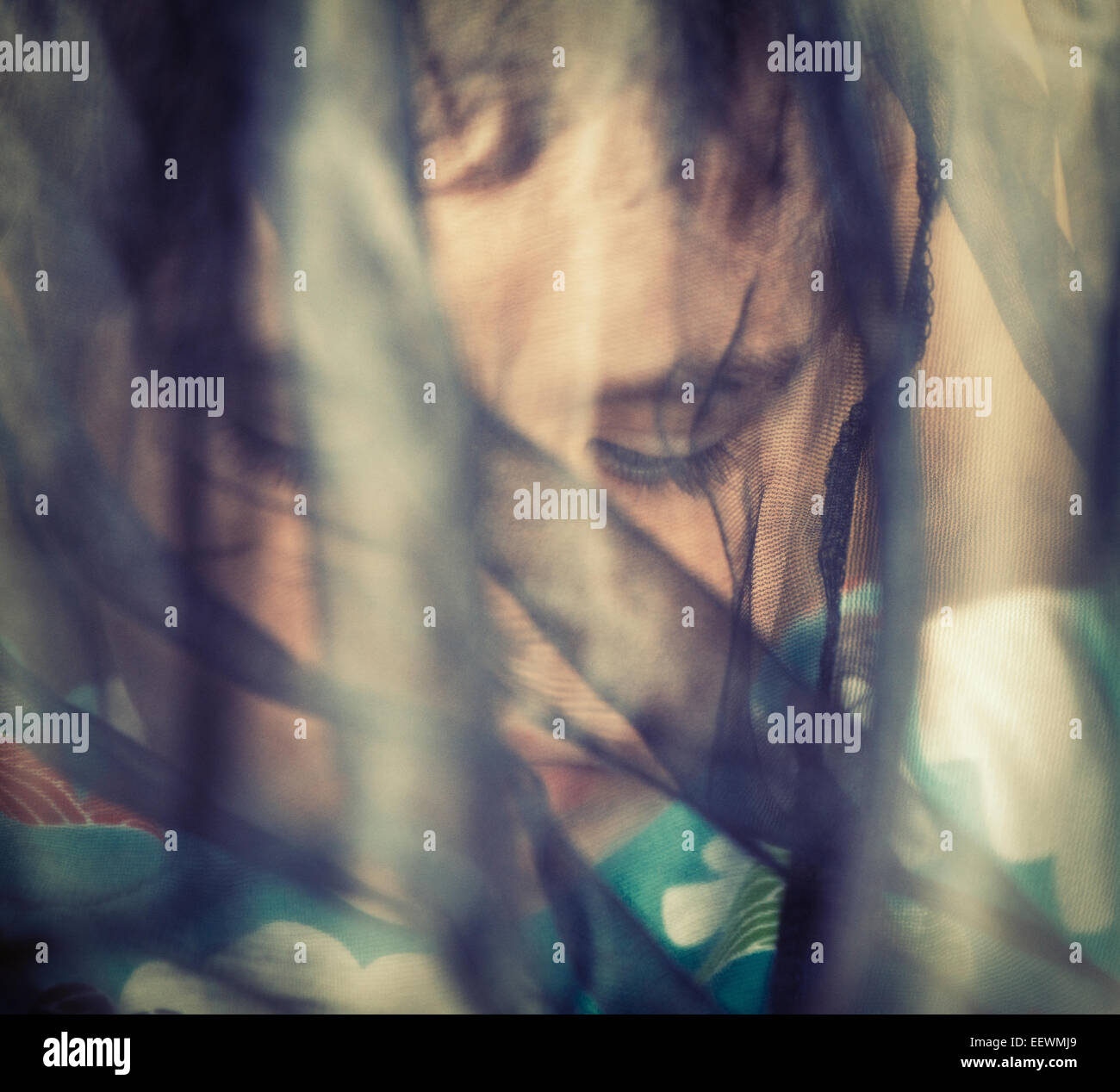 Portrait of girl with fabric, veil covering her face She looks troubled and pensive Conceptual image of childhood - Stock Image