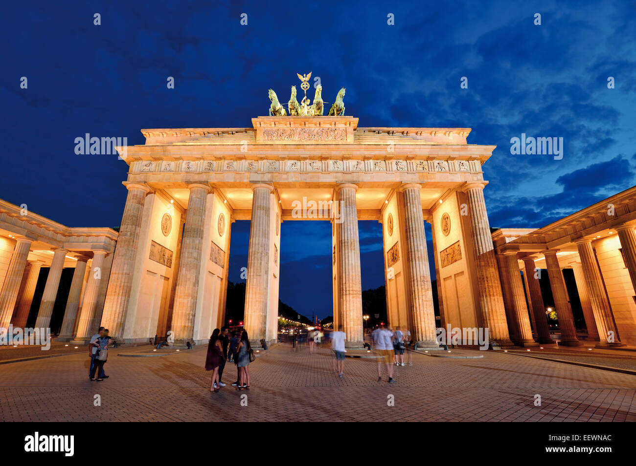Germany, Berlin: People taking pictures in front of the Brandenburg Gate at night - Stock Image