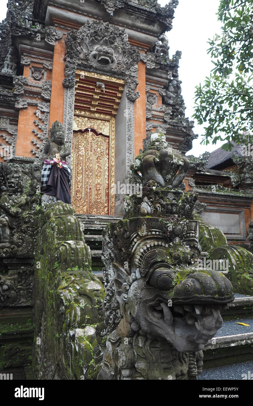 Statue of a dragon guarding the kori agung gate at Pura Taman Saraswati, Ubud, Bali. - Stock Image