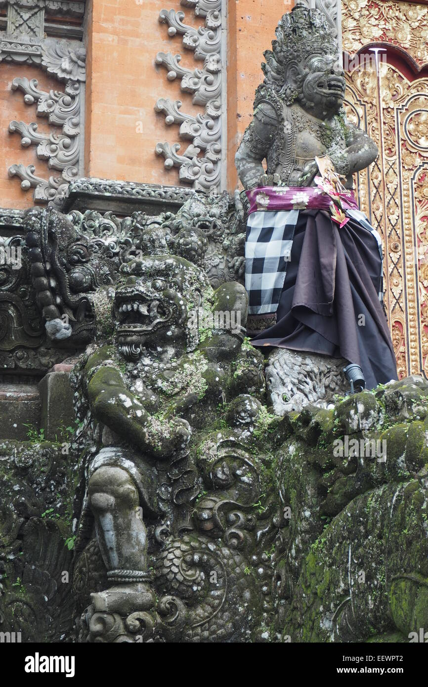 Decorative stone statues guarding the kori agung gate at Pura Taman Saraswati Ubud, Bali. - Stock Image
