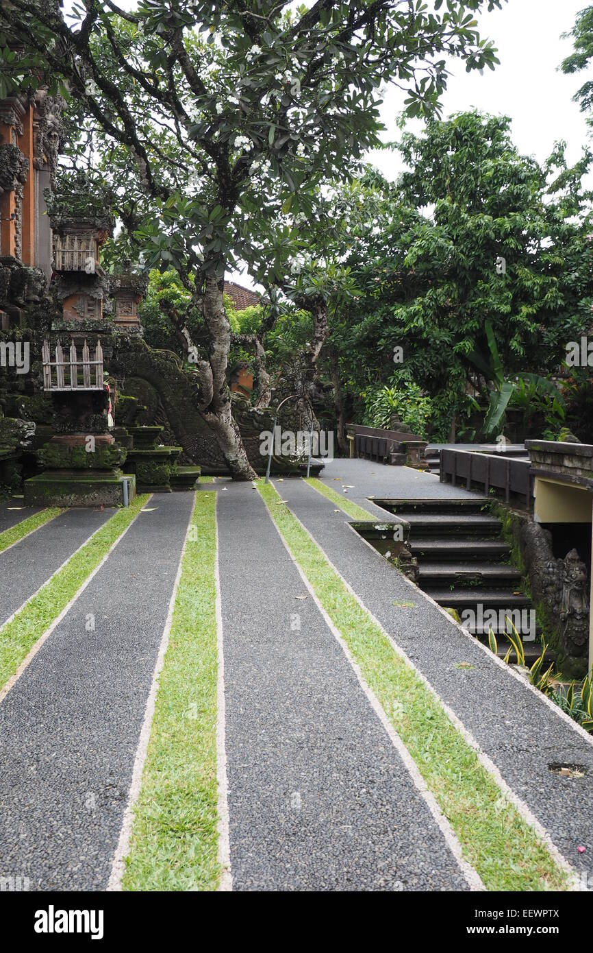 Parallel lines of grass and pavement in front of the kori agung gate at Pura Taman Saraswati Ubud, Bali. - Stock Image