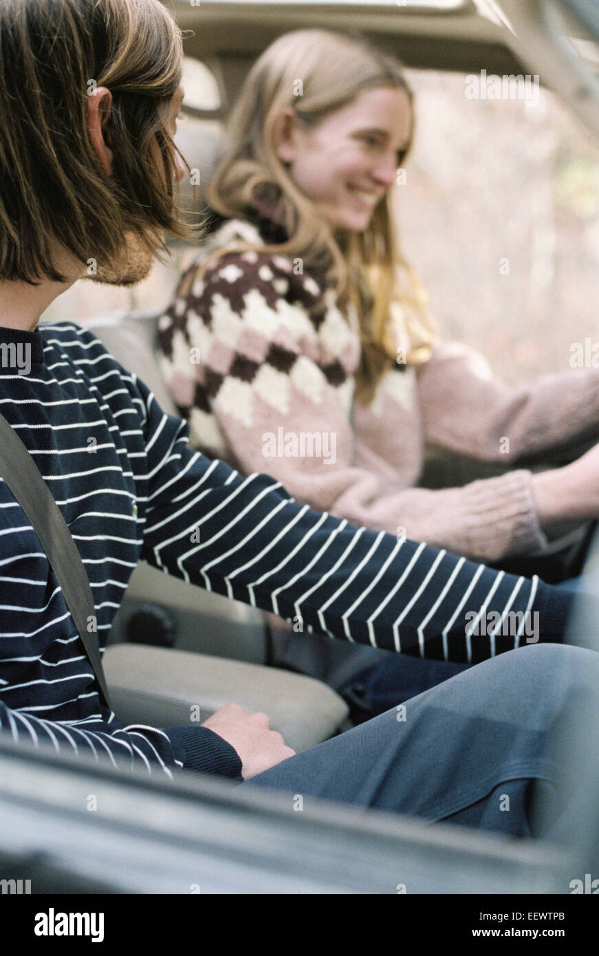 Smiling young couple driving in their car. - Stock Image