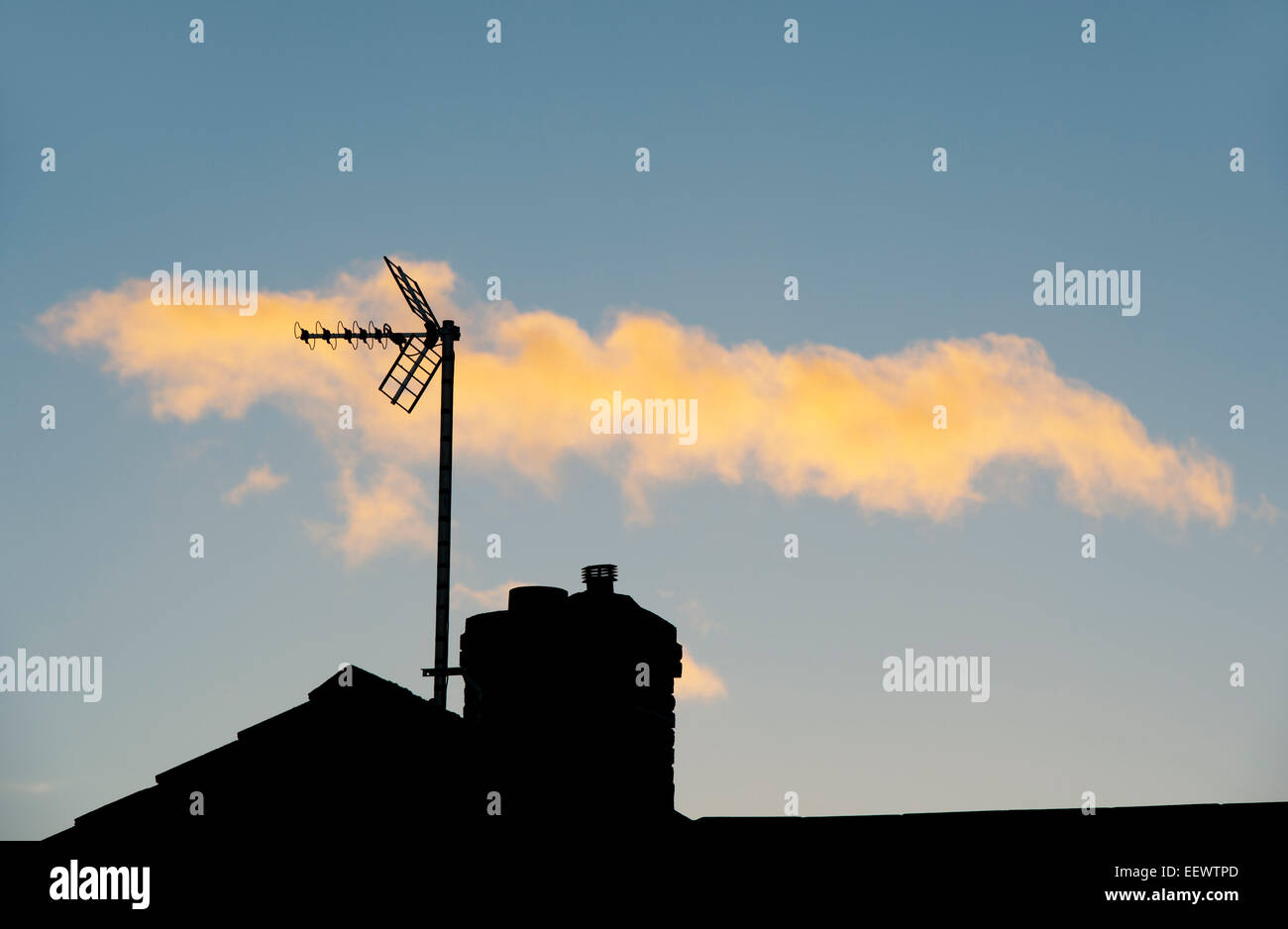 Silhouette TV aerial and house chimney against a sunset cloudy sky - Stock Image