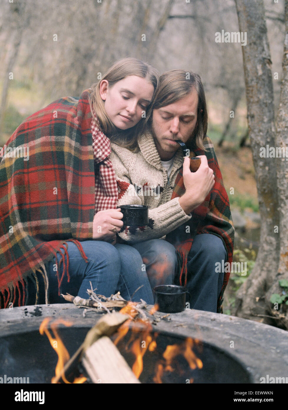 Young couple sitting by a fire pit, wrapped in a blanket. - Stock Image