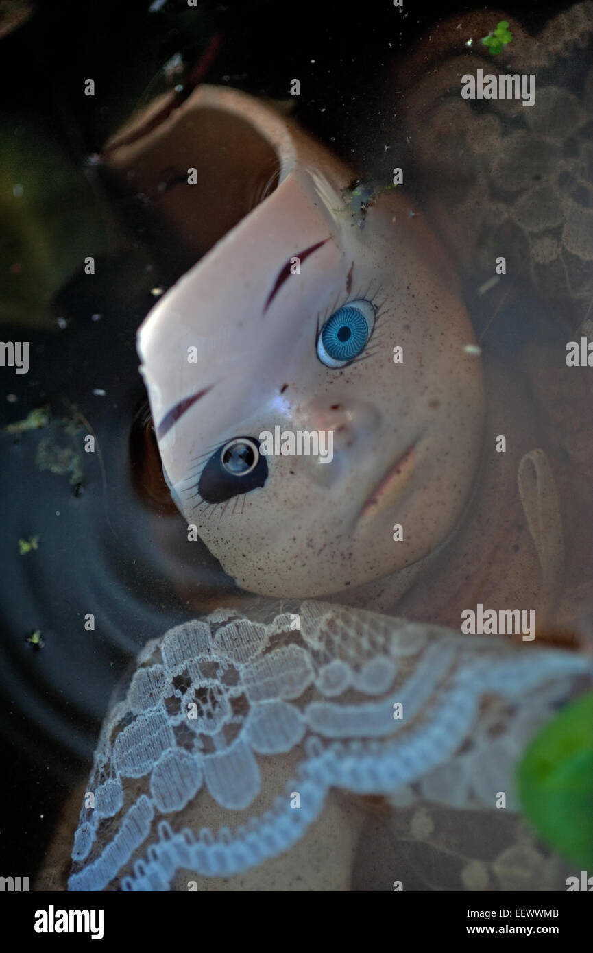 disgarded doll in pond - Stock Image