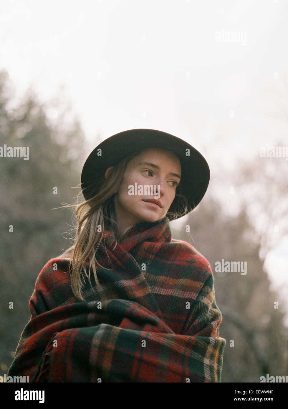 Young blond woman wearing a hat, wrapped in a blanket. - Stock Image