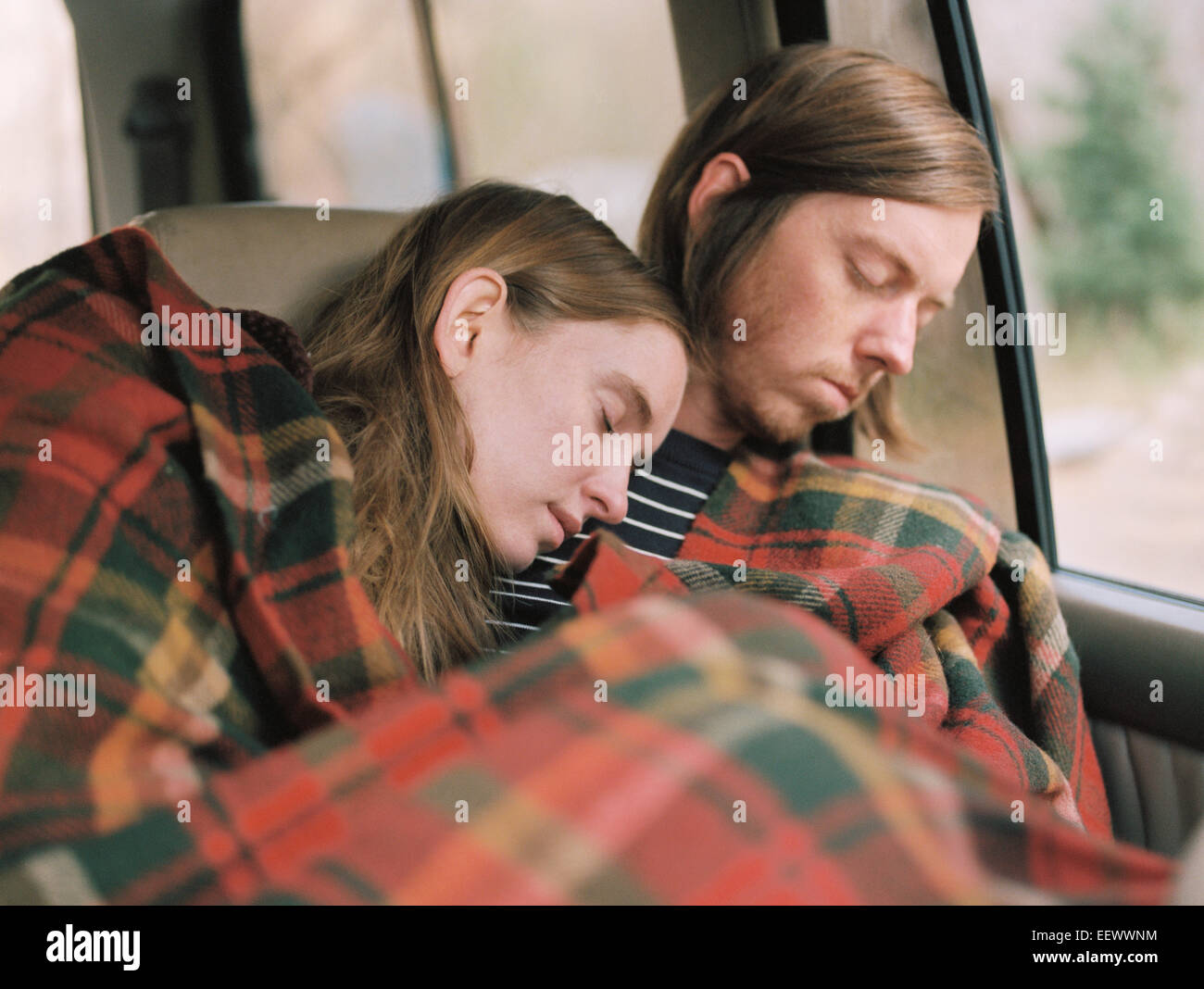 A couple taking a nap in their car, covered by a blanket. - Stock Image
