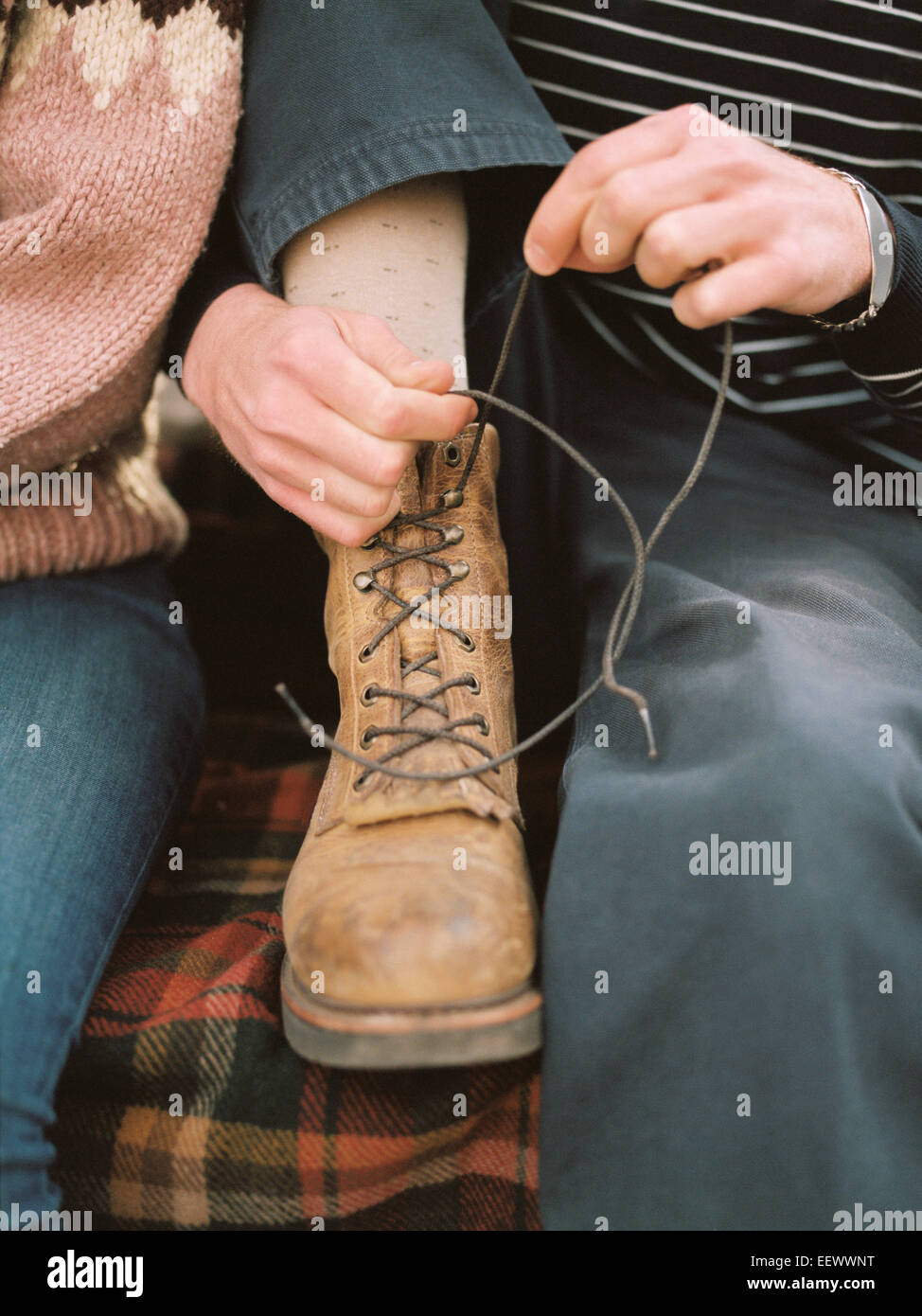 Close up of a man tying his boot laces. - Stock Image
