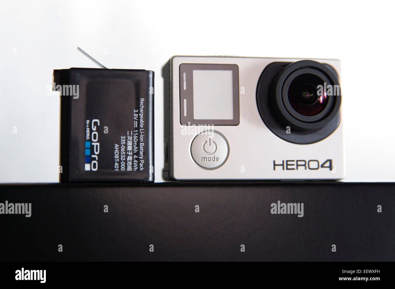 A GoPro Hero 4 Black edition is pictured in a studio with a battery on a white background. - Stock Image