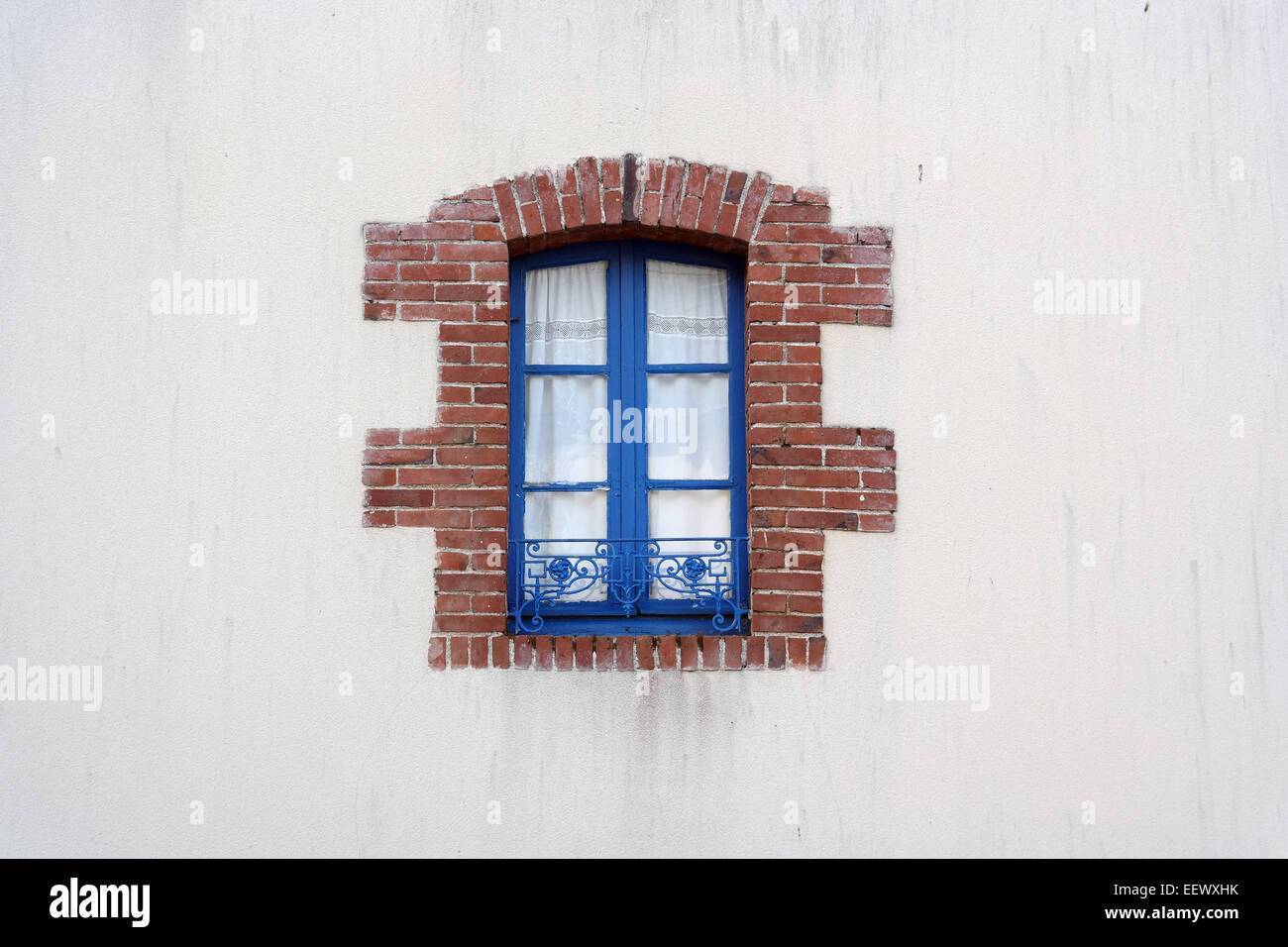 Blue metal Window frame edged with bricks on white House in Brittany ...