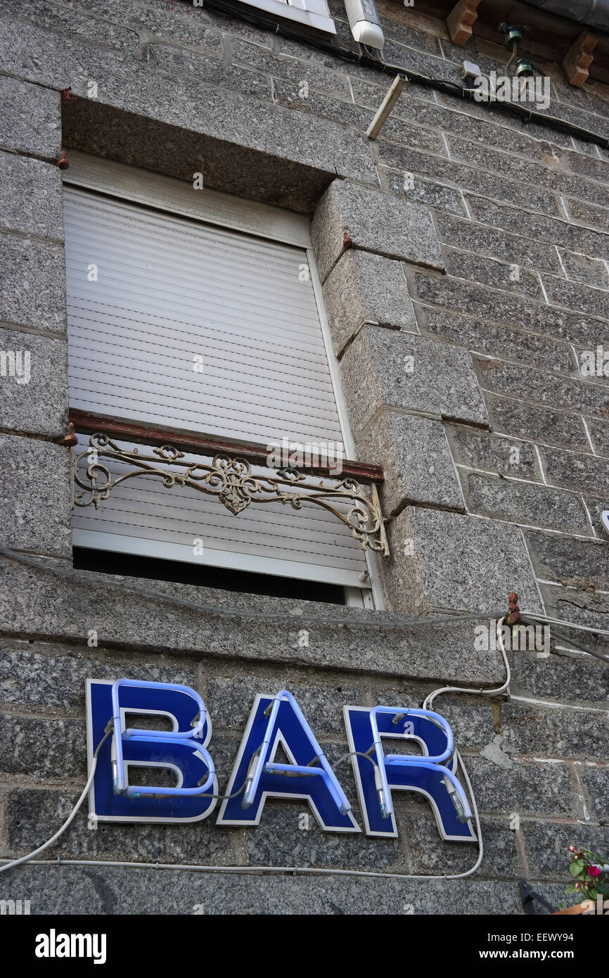 Bar Neon sign under a closed window of a facade - Stock Image