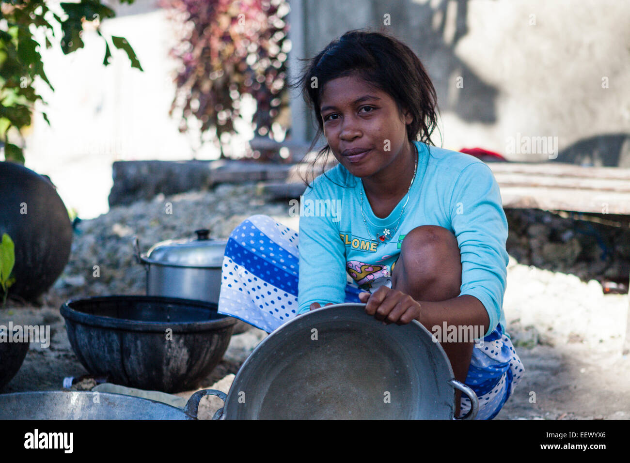 Young woman rinsing pan, Pulau Manggur, Kai Islands, Moluccas, Indonesia - Stock Image