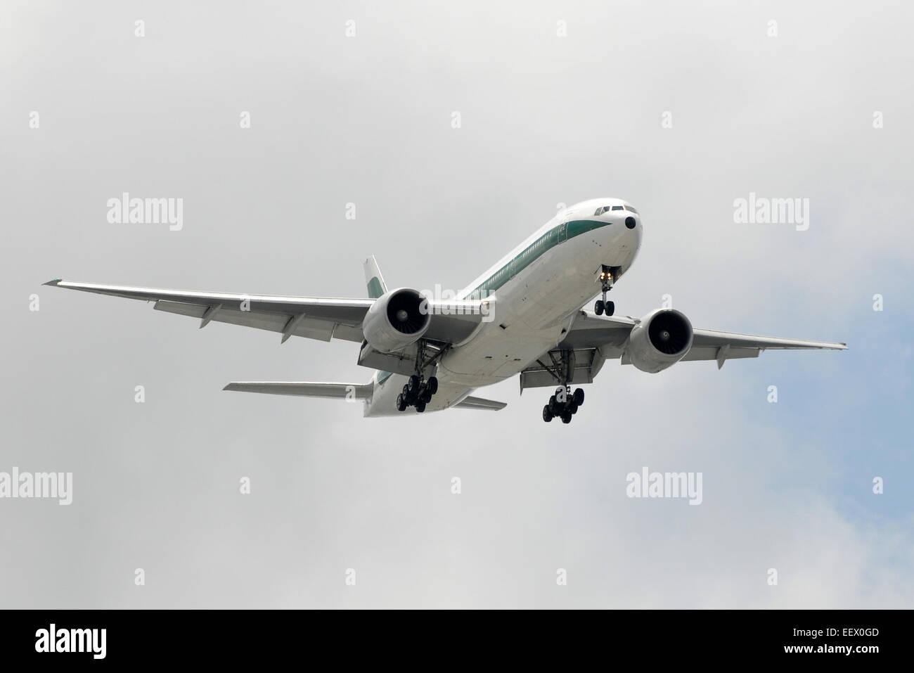 Modern passenger jet airplane approaching for landing Boeing 777 - Stock Image