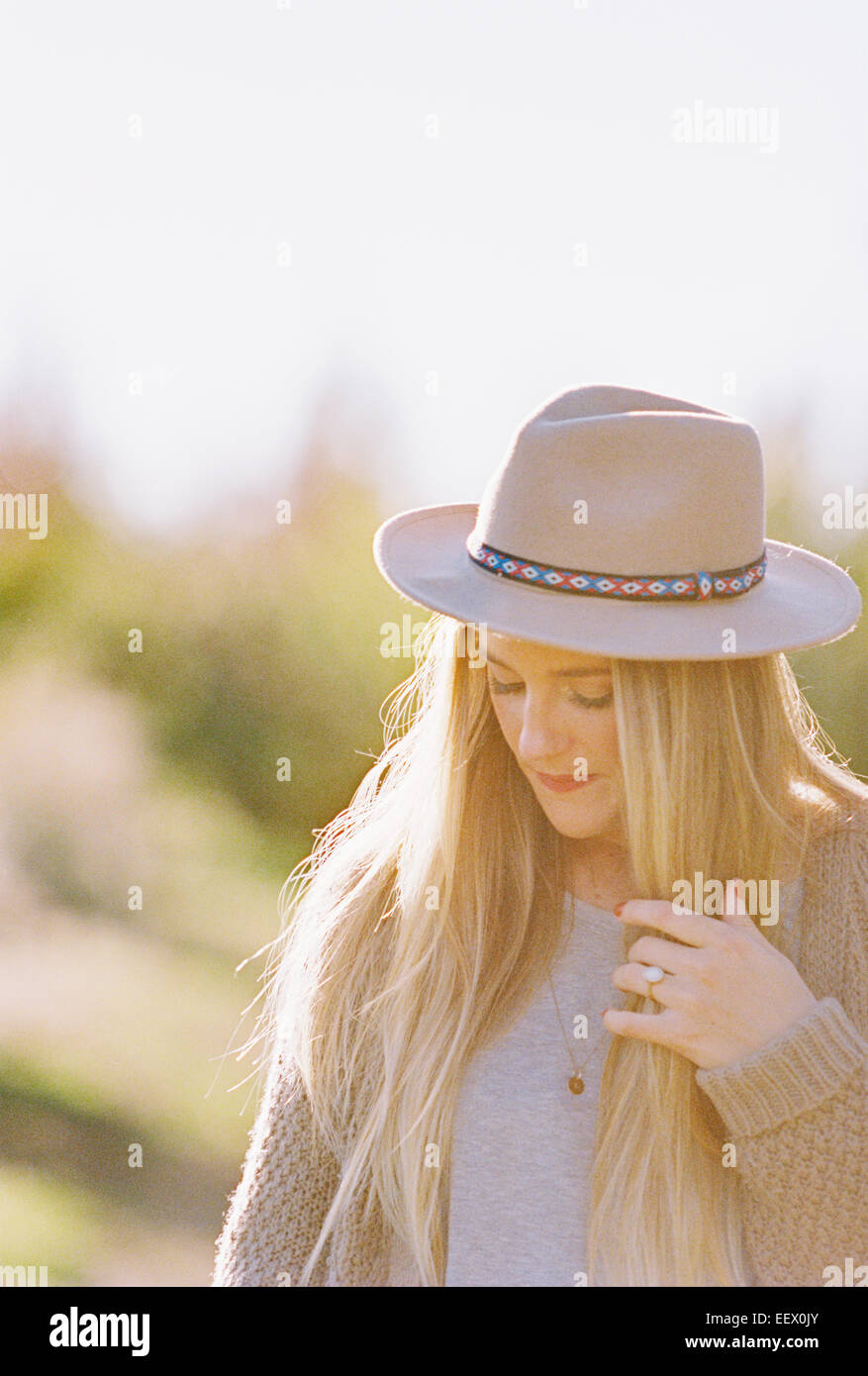Woman with long blond hair, wearing a hat. - Stock Image