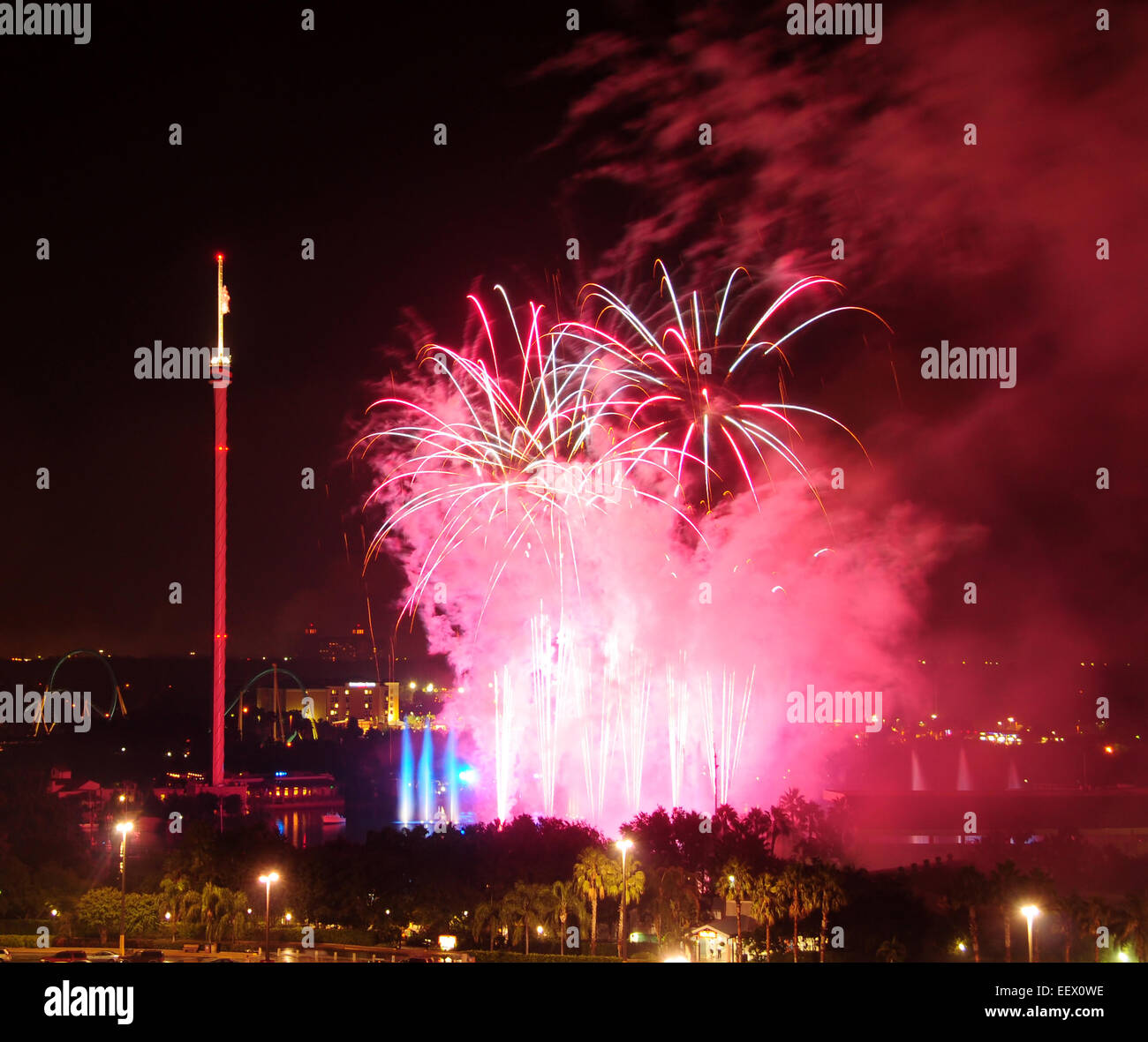 Red and purple fireworks against night sky - Stock Image